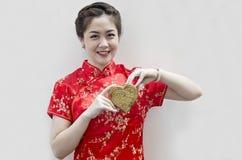 Cheongsam d'usure de femme et coeur d'or de fixation Photographie stock