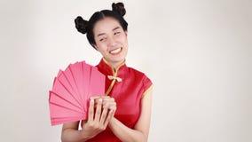 Cheongsam del desgaste de mujer y sobre el sostenerse en concepto de Año Nuevo chino feliz metrajes