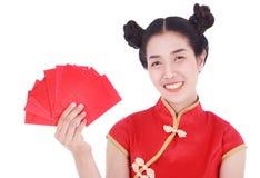 Cheongsam del desgaste de mujer y sostener el sobre rojo en el concepto de happ Fotos de archivo libres de regalías