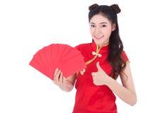 Cheongsam del desgaste de mujer y sostener el sobre rojo en el concepto de happ Imágenes de archivo libres de regalías