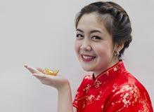 Cheongsam di usura di donna ed oro del cinese della holding Fotografia Stock