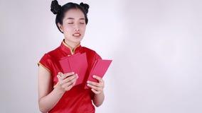 Cheongsam di usura di donna e busta di conteggio nel concetto del nuovo anno cinese felice stock footage