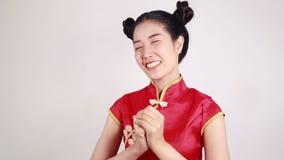 Cheongsam för kvinnakläder med gest av lyckönskan i begrepp av det lyckliga kinesiska nya året