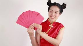 Cheongsam för kvinnakläder och hållande kuvert i begrepp av det lyckliga kinesiska nya året