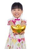 Cheongsam que lleva de la niña china asiática que sostiene el lingote del oro Foto de archivo