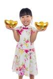 Cheongsam que lleva de la niña china asiática que sostiene el lingote del oro Fotografía de archivo