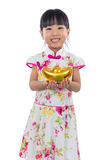 Cheongsam que lleva de la niña china asiática que sostiene el lingote del oro Fotos de archivo libres de regalías