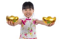 Cheongsam que lleva de la niña china asiática que sostiene el lingote del oro Imagen de archivo libre de regalías