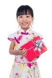 Cheongsam que lleva de la niña china asiática que sostiene la caja de regalo Imagen de archivo