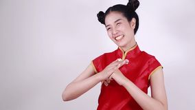 Cheongsam rojo del desgaste de mujer con el gesto de la enhorabuena en concepto de Año Nuevo chino metrajes