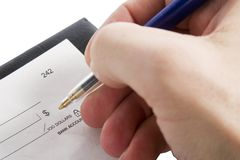 Cheque Amount. A male hand filling out the amount on a cheque. Isolated on white with clipping path royalty free stock image
