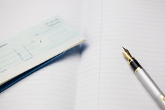 Cheque Book and Pen. A view of a silver pen  with a blank cheque  on a note book Royalty Free Stock Photography