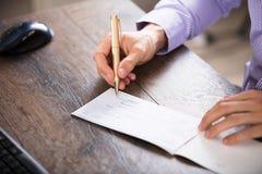 Cheque de firma de la mano del ` s del empresario Foto de archivo