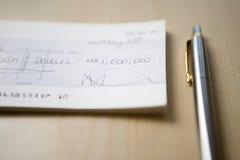 Cheque para un millón dólares que mienten al lado de pluma en el primer de la tabla Imagen de archivo libre de regalías
