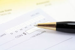 Cheque with pen Stock Photos