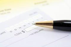 Cheque with pen Stock Photos