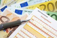 Cheque and pen on heap of euro notes Royalty Free Stock Images