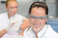 Chequeo protector del paciente de los vidrios del dentista profesional imagen de archivo