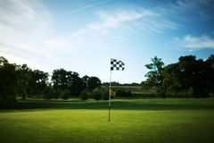Chequered flag on a golf course green with a blue sky stock photography