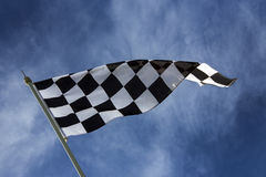 Chequered Flag - Winner. The chequered flag is used to end a motor race. The flag is commonly associated with the winner of a race, as they are the first stock photos