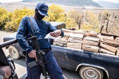 Cheran: il membro della polizia volontaria controlla un permesso della raccolta della legna da ardere Immagine Stock