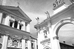 """Cherasco, Cuneo. Black and white photo. View of the """"Arco del Belvedere"""" and the Sant'Agostino Church facade in Cherasco, little village in the Province of Royalty Free Stock Photo"""