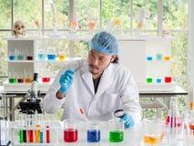 Chercheur asiatique de chimiste regardant un comprimé le laboratoire, le scientifique vérifiant la médecine images stock