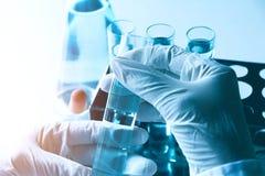 Chercheur avec les tubes à essai chimiques de laboratoire en verre avec le liquide Images libres de droits