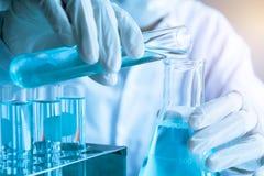 Chercheur avec les tubes à essai chimiques de laboratoire en verre avec le liquide Images stock