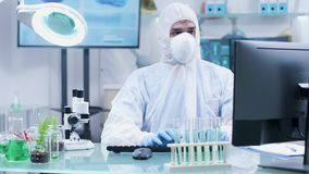 Chercheur biologiste dans la combinaison blanche et masque travaillant sur l'ordinateur banque de vidéos