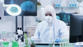 Chercheur biologiste dans la combinaison utilisant une règle pour mesurer la longueur d'usine banque de vidéos