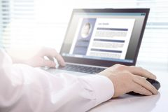 Chercheur d'emploi et demandeur écrivant son résumé et cv avec l'ordinateur portable image stock