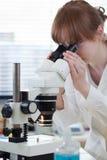 Chercheur féminin à l'aide d'un microscope Photo stock