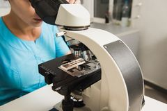 Chercheur féminin avec un microscope images libres de droits