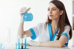 Chercheur féminin chimique tenant le flacon dans le laboratoire image libre de droits