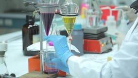 Chercheur féminin de laboratoire dans l'usage protecteur jugeant en verre avec le chem banque de vidéos