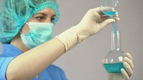 Chercheur faisant l'expérience dans le laboratoire mélangeant deux le liquide, médecine, vaccin photos libres de droits