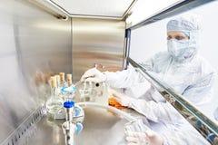 Chercheur féminin travaillant avec le matériel dangereux de virus de risque Photographie stock libre de droits