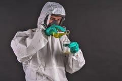 Chercheur masculin analysant le réactif liquide en verrerie de laboratoire image stock