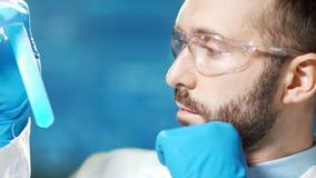 Chercheur masculin professionnel secouant le becher en verre avec la vue de côté réactive bleue banque de vidéos