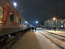 A stop of long-distance train on a winter snowy evening under light of lanterns. Travel with the company Russian Railways stock images