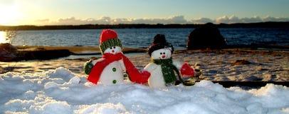 Cherful snowmans που περπατά κατά μήκος της παραλίας στο χιόνι στοκ εικόνες