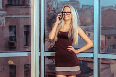 Cherful young blonde lady talking phone and smiling on camera. Business woman talking phone. City views behind the window in the office Stock Image