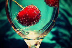 Cheries. In a glass of mineral water covered with bubbles Royalty Free Stock Photos