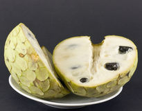 Cherimoya divided on black bottom. Cherimoya divided in a plate on black bottom Royalty Free Stock Image