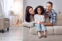 Happy girl with her loving parents. We cherish you. Nice exuberant curly-haired girl smiling and sitting on the couch and her parents standing behind her Royalty Free Stock Photo