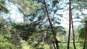 Cherkasa, Ukraine-May 1, 2018: The visitors enjoy their treetop adventure, climbing on the wooden block hanging with the. Cherkasa, Ukraine-May 1, 2018: pine stock video