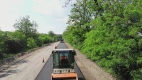 CHERKASSY REGION, UKRAINA - MAJ 31, 2018: Flyg- sikt på reparationen av en huvudväg, vägbyggnationer Rullcompactor stock video