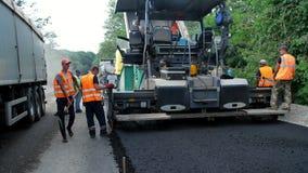 CHERKASSY REGION, UKRAINA - MAJ 31, 2018: reparation av en huvudväg, vägbyggnationer Arbetare lägger asfalt Det finns arkivfilmer