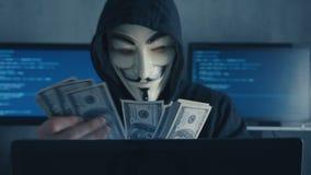 Cherkassy, Ucrania, el 10 de enero de 2019: Anónimo en la máscara de Guy Fawkes cuenta de nuevo cuentas de los dólares ganados co almacen de video